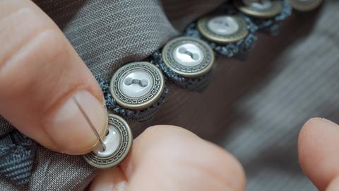 Hände nähen einen Knopf an einer Knopfleiste an.
