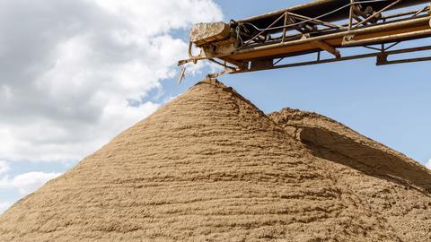 Abgebauter Sand türmt sich unter einem Förderband.