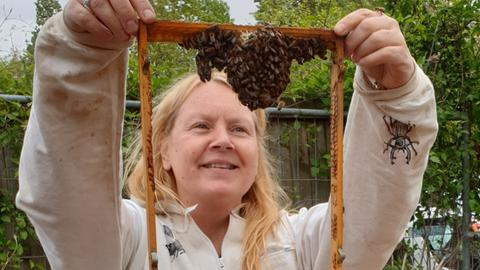 Imkerin hält eine Bienenwabe in die Luft und freut sich.