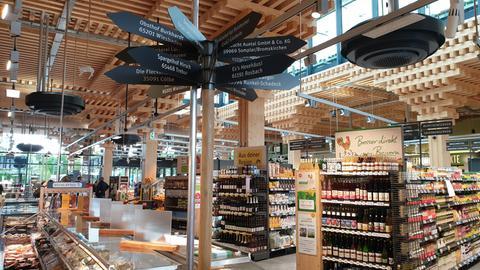 Wegweiser und volle Regale in einem besonderen Wiesbadener Lebensmittelsupermarkt.