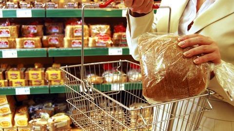 Eine Frau steht vor einem Brotregal im Supermarkt und packt geschnittenes, abgepacktes Brot in ihren Einkaufskorb.