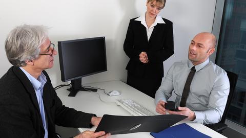Ein älterer Mann hat bei einem Personalchef und seiner Assistentin ein Bewerbungsgespräch und reicht seine Bewerbungsmappe über den Schreibtisch.