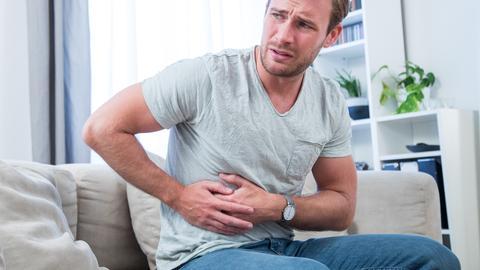 Ein junger Mann sitzt in einem Wohnzimmer und fässt sich mit schmerzverzerrtem Gesicht an den Bauch.
