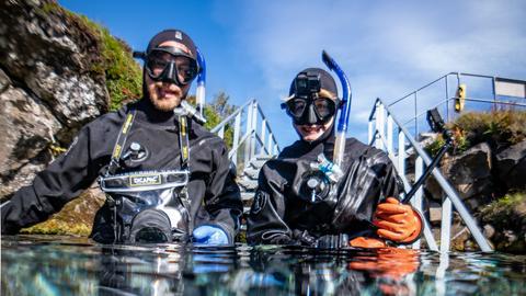 Nina und Jonas stehen mit Schnorchel-Ausrüstung im klaren Wasser.