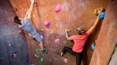 Ein junger Mann und eine junge Frau klettern an einer Boulder-Wand hoch.