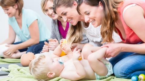 Einige Mütter und Kleinkinder spielen.