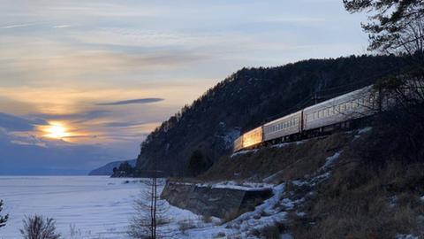 Eisenbahn fährt an einer Schneelandschaft vorbei, die Sonne geht gerade unter.