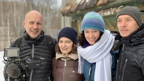 Protagonisten posieren für ein Erinnerungsfoto vor einer Hütte.