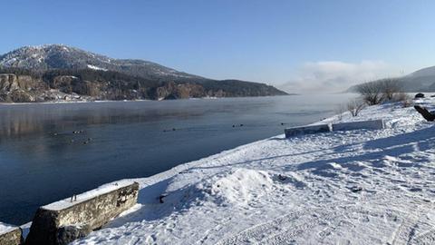 Verschneite Landschaft mit Blick aufs Wasser.