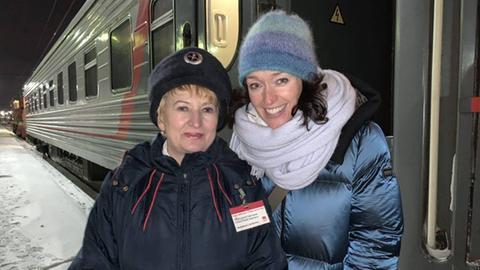 Protagonistinnen machen vor der Transsibirischen Eisenbahn ein Foto.