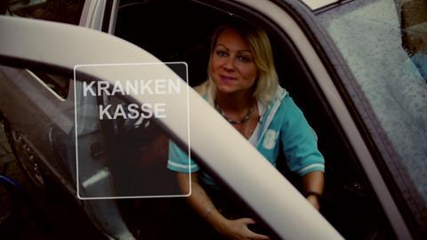 """Protagonistin sitzt im Auto und schaut zur Tüer heraus. Symbol: Viereck mit Text """"Krankenkasse""""."""
