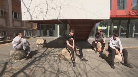 Vier Jungs sitzen auf Steinen vor einem Gebäude.