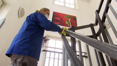 Protagonist wischt mit einem Lappen über das Treppengeländer in einem Treppenhaus.