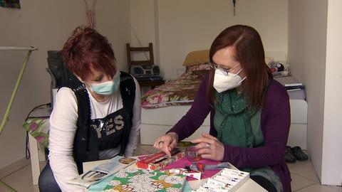 Zwei Protagonistinnen malen in einem Zimmer gemeinsam mit bunten Acrylfarben auf Leinwand.