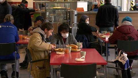 Zwei Protagonisten sitzen in einer vollen Kantine und essen.