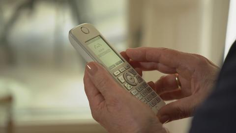 Eine ältere Frau hält den Hörer eines schnurlosen Telefons in den Händen.