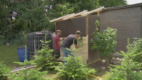 Sascha Möller und Tobias Wagner verkleiden den Gartenschuppen.