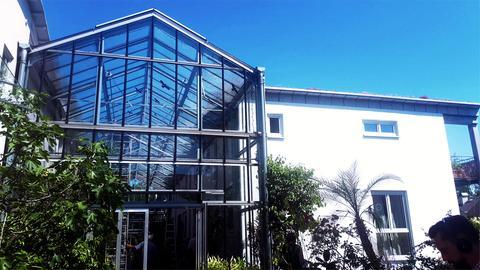 Ein Glashaus steht zwischen zwei Häusern mit weißer Fassade.
