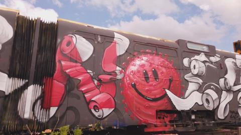 Mit Graffitis angesprühter Eisenbahnwagon: ein roter Smiley.