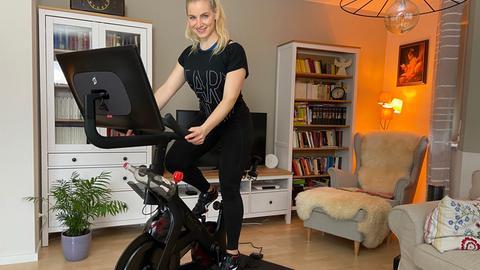 """Ratgeber-Reporterin Maike Tschorn """"fährt"""" auf ihrem Homecycling-Gerät im Wohnzimmer."""