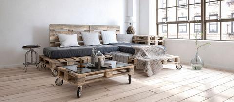 Blick in ein loftartiges Wohnzimmer mit Paletten-Sofa und Paletten-Beistelltisch.