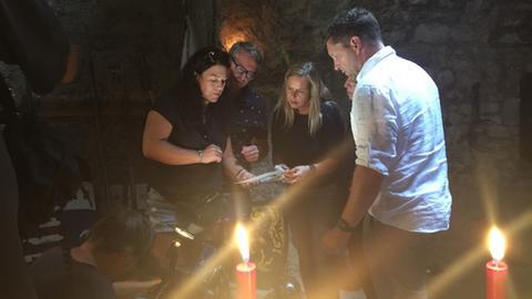 Mehrere Männer und Frauen stehen um eine Schatzkarte herum und lesen sie bei Kerzenschein in einem Gewölbe.