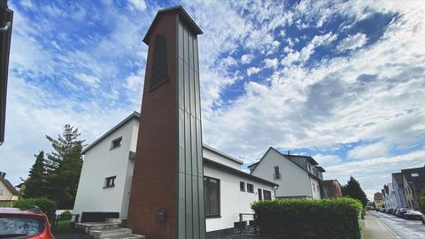 Kirchturm neben weißem Wohnhaus.