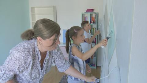 Milla und ihre Familie bemalen eine Wand ihres Zimmers.