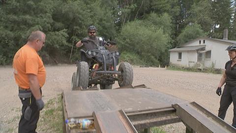 Ein Mann fährt mit seinem Quad eine Rampe hoch.