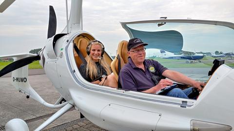 Ratgeber-Reporterin Maike Tschorn und ihr Pilot bestens gelaunt auf einem Flugplatz im Gyrocopter.