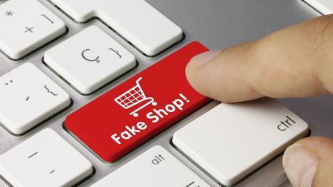 """Computertastatur mit roter Taste, auf der in weißer Schrift steht: """"Fake Shop!"""" und ein Zeigefinger, der auf diese Taste drücken will."""