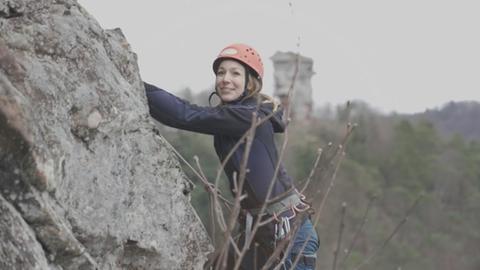 Die ehemalige Weinprinzessin Christina Fischer klettert gesichert und mit Helm an einem Steinfelsen hoch.