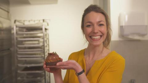 Christina Fischer hat ein Schokoladentörtchen in der Hand und strahlt.