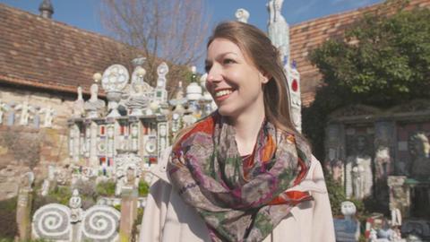Christina Fischer steht in einem Garten mit künstlerischen bunten Skulpturen.