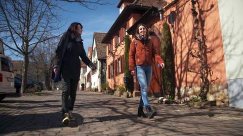 Protagonistinnen spazieren eine Straße entlang.