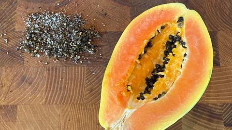 Pfeffer aus Papayakernen neben aufgeschnittener Papaya