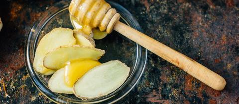 Ein Honiglöffel voller Honig und mehrere dünngeschnittene Scheiben Ingwer auf einer kleinen Glasplatte.