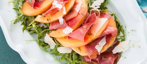 Ein Rucola-Melonen-Salat auf einem Teller.