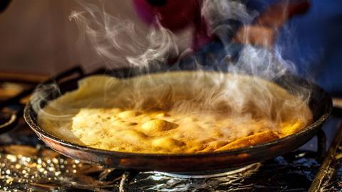 Crêpe wird in einer Pfanne gebraten
