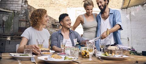 Freunde essen zusammen an einem Tisch im Sommer.