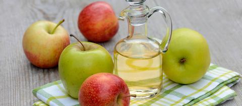 Karaffe mit Apfelessig und Äpfeln