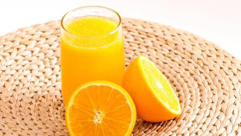 Orangensaft im Glas mit Orangenhälften