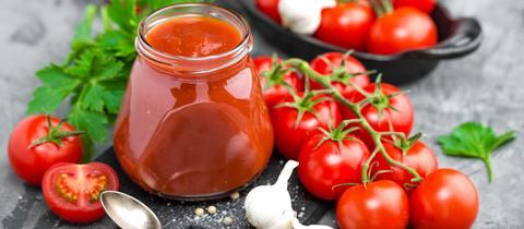 Gläschen mit Tomatensoße, Tomaten, Knoblauch und Kräutern