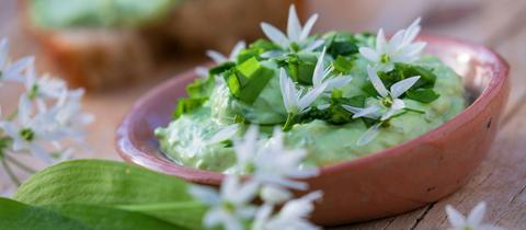 Bärlauchcreme im Schälchen mit Blüten dekoriert