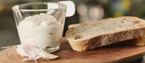 vegane Mayonnaise aus Kichererbsenwasser im Glasschälchen und mit Brotscheibe angerichtet