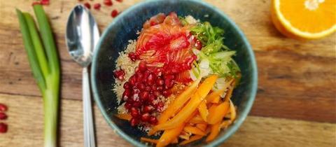 Fertig angerichtete Bowl mit Lachs und Gemüsecouscous