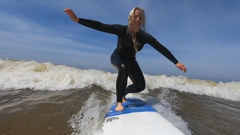 Ratgeber-Reporterin Maike Tschorn surft mit den Wellen im Meer.