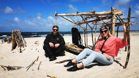 Ratgeber-Reporterin Maike Tschorn sitzt bei strahlendem Sonnenschein mit einem weiteren Protagonisten am Strand vor einem Treibholzgerüst.
