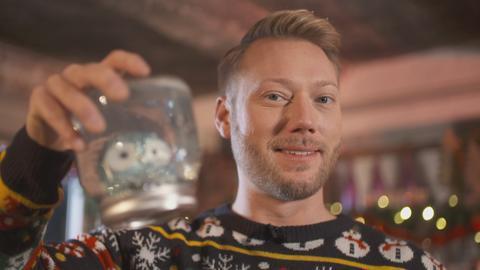 Jens Pflüger mit einer Schneekugeln, gebastelt aus einem Einmachglas.