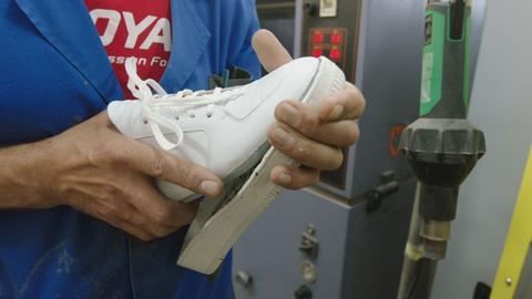 Die Schuhsohle wird per Hand an einem Turnschuh befestigt.